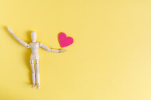 A Wooden Figurine Holding A Red Heart At Arm's Length. Mannequin And Heart On A Bright Yellow Background Of Kopi Space