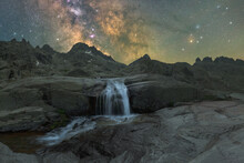 Waterfall In Mountains Under Sunset Sky With Milky Way