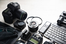 Professional Photographic Equipment And Digital Photo Edit And Retouching.Digital Photo Workstation Over Black Background.Top View Of  Digital Camera, Flash,lens And Laptop.