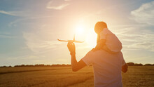 Young Father Carries Toddler Son On Shoulders And Toy Red Plane In Hand And Turns Round Flying Airplane In Yellow Field At Sunset Light, Sunlight