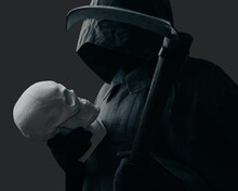 Grim Reaper With A Scythe Looking At Skull On A Dark Background. Death In A Black Cloak With A Hood.