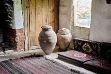 Inside The Old And Abandoned Village House Made Of Wooden Material And There Are Large Size Earthenware Jars Near The Window And Antique Style Carpets And Ingle.