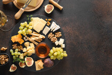 Cheese Platter With Grapes, Nuts, Figs On A Brown Background. Top View. Festive Gourmet Appetizer For Holiday.
