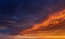 Vibrant Sunset Sky With Dark Clouds Illuminated By Orange Sunlight
