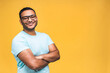 Portrait of a cheerful young african american indian black man standing isolated over yellow background.