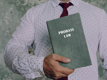 Jurist Holds PROBATE LAW Book. Probate Lawrefers To The Process That Manages Any Assets And Debts Left Behind By A Deceased Person