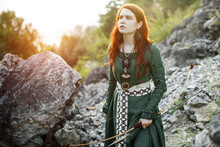 Beautiful Red-haired Girl-archer Of Middle Ages Among Rocks. Fantastic Concept