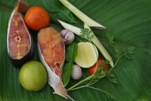 Food Ingredients. Cut Fresh Raw Fish Meat And Thai Herbal Vegetables For Cooking On Green Leaf For Tom Yum Menu. Organic Food For Healthy Nutrition. Concept : Local Thai Food.