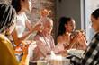 Leinwandbild Motiv Multiracial young women talking and eating pizza while having break