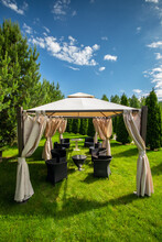 White Canvas Gazebo With Plastic Garden Furniture In A Summer Green Lawn. Vertical, Copy Space.