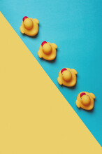 Four Yellow Rubber Ducks On A Blue And Yellow Background. Bath Concept. Copy Space, Flat Lay.
