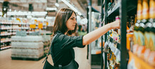 Young Woman Choosing Beer In A Supermarket