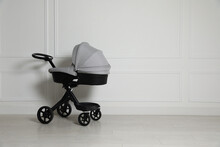 Baby Carriage. Modern Pram Near White Wall, Space For Text