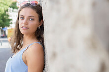 Portrait Of Young Woman Smiling And Leaning Agains A Wall