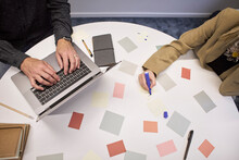 Business People Using Sticky Notes And Laptop In Office