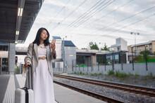 Woman Using Phone At Train Station Platform