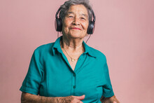 Happy Elderly Woman Listening To Music In Headphones