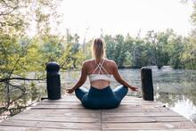 Serene Ethnic Woman Meditating In Lotus Pose On Pier