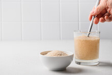 Woman Adds Spoon Psyllium Fiber And Mix Up In Glass Of Water On A Kitchen White Background. Superfood For Healthy Intestines And Gluten Free Diet.