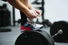 Man Tying His Boot On The Barbell In The Gym