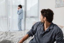 Man Standing And Looking At Window With Blurred Boyfriend On Foreground, Relationship Difficulties Concept