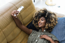 Delighted Black Woman Taking Selfie At Home