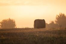 Sunrise In The Field. The Soft Morning Light Illuminates The Hay Bale. Belarusian Landscape.