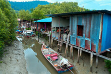 Fishermen's Village In Asia. Boats Near Dilapidated Houses On Stilts