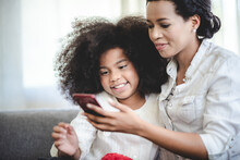 Cheerful Young Mother Taking A Selfie Using Smartphone With Sister With Curly Hair While Making Funny Facial And Hand Gestures Sitting On Couch At Home