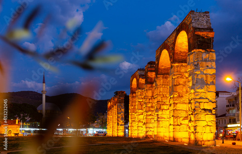 View of illuminated ruins of ancient Byzantine aqueduct in Selcuk at twilight, Turkey