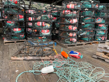 Setting Up Round Crab Trap At Harbor Warehouse With Tall Stacks Of Crab Traps In The Background