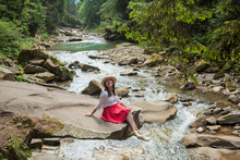 Happy Smiling Girl In A Straw Hat, White Blouse, Red Skirt And Yellow Sneakers Sitting Near Mountain River. Young Woman Enjoys Fresh Air In Forest Resting On A Rock Above A Waterfall. Lonely Travel