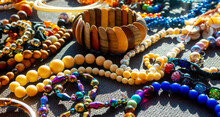 A Lot Of Costume Jewelry With Different Materials On A Black Background