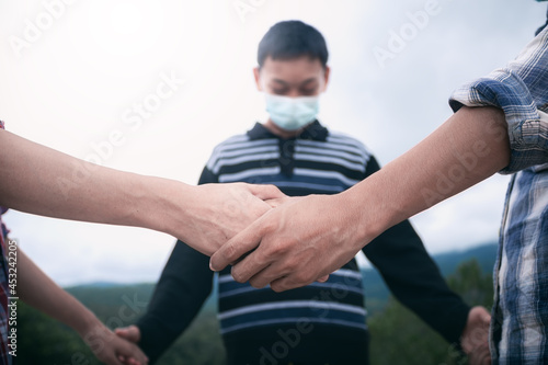 Fototapeta Youth group team holding hands and pray for healing