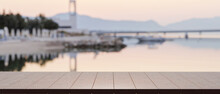 Empty Of Wood Table Top For Product Display With Blurred  Lake Harbour View In The Background