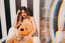 Smiling Model With Toy Bear On Striped Background