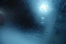 Drops Of Rain On Blue Glass Background. Street Bokeh Light Out O