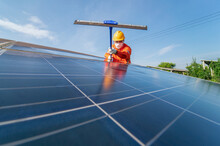 Washing The Surface Of The Solar Panels Which Are So Dirty With Dust And Pigeon's Droppings On The Roof