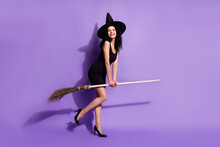 Full Size Photo Of Happy Smiling Good Mood Beautiful Girl Witch Riding Broomstick Isolated On Purple Color Background