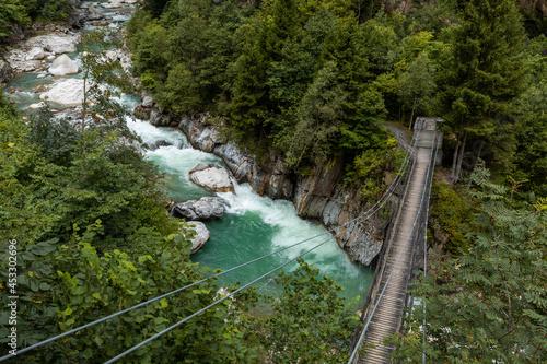 Suspension bridge over the Reuss river with rapids at Gurtnell in German-speaking Switzerland.