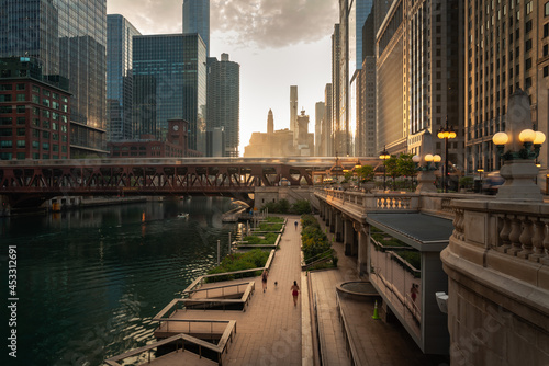 Beautiful downtown Chicago morning along the river as people jog on the path below and train crosses a bridge as the sun casts yellow light into the scene from behind the high-rise buildings beyond.