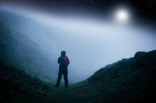 A Concept Edit Of A Lone Hooded Hiker  On A Path In The Countryside Looking Up On A Cold Spooky, Foggy Night With Stars Above