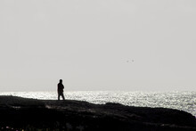 Man Walking Along Cliff Over Ocean In Jacket With Arms Wrapped Around Himself And Two Birds Flying In Grey Sky - Monotone Evening.