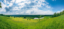 Summer Panoramic Landscape With Wildflowers And Trees On A Wide Meadow, A Winding River And A Forest In The Distance, Clouds In The Blue Sky.