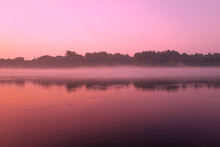 Pink Sunrise Over The Cape Cod Canal. Symmetrical Reflections Of The Sky And Forest Over The Water Surface.