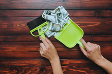 Two Female Hands Hold A Brush And Scoop And Remove Dollar Bills From The Wooden Table. The Concept Of Devaluation, Depreciation, Inflation And Default, When Money Loses Its Value.