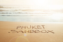 Phuket Sandbox Text Written In The Sand On The Beach In Phuket, Thailand With Incoming Wave