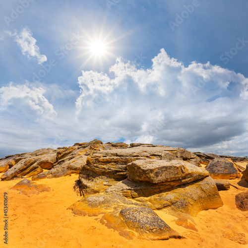 sandy desert with heap of huge stones at sunny day