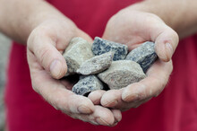 The Man Holds The Rubble In His Palms. Pieces Of Random Granite