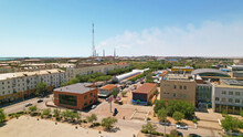 Drone View Of The Small Town Of Balkhash. The City Is Located On The Shore Of A Lake. Low Houses, Free Streets And Roads. Green Trees Grow And There Are Sports Grounds. There Is A Steppe Around City